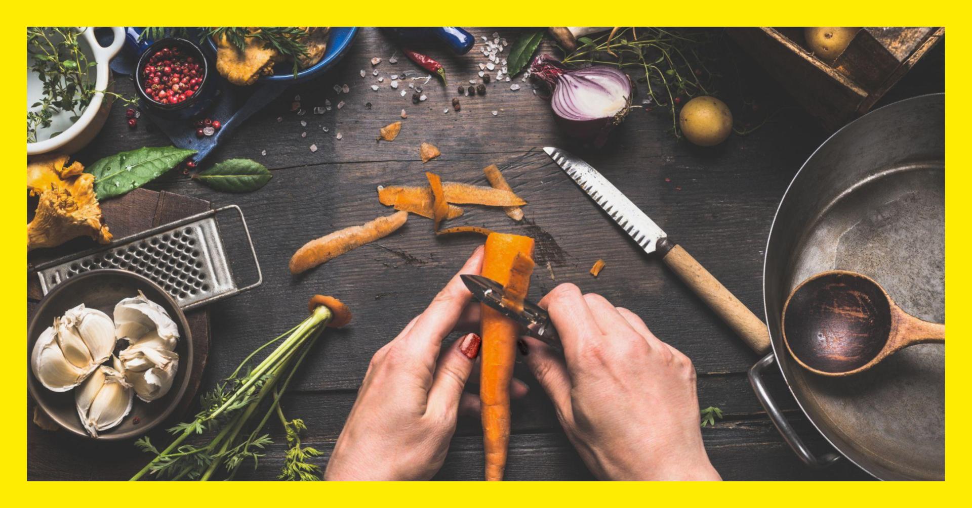 kädet kuorii porkkanaa, pöydällä vihanneksia